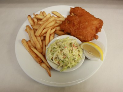 Halibut dinner served with chips and coleslaw.